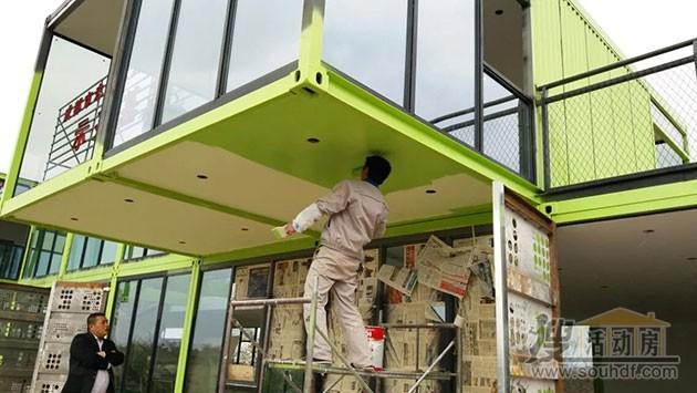 工人们正在集装箱房屋底部找平,粉刷