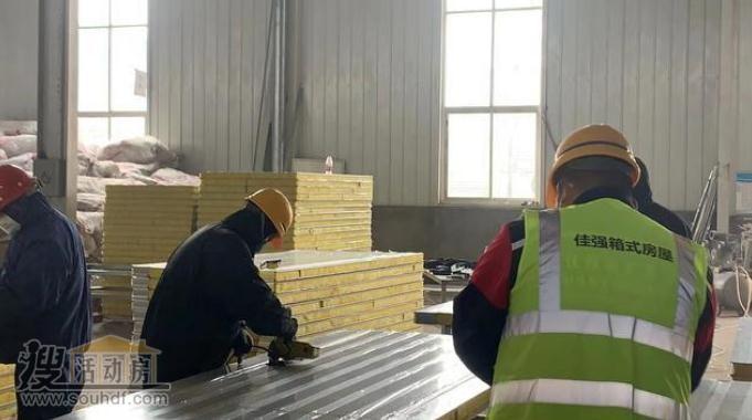 工人们正在加班生产打包箱房屋